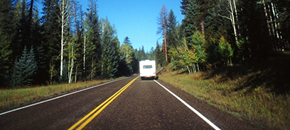 Photo of an RV driving down a road. A forest surrounds the road.