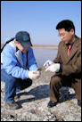 NWDP biologist Janean Romines teaches a Chinese workshop participant to collect environmental samples.